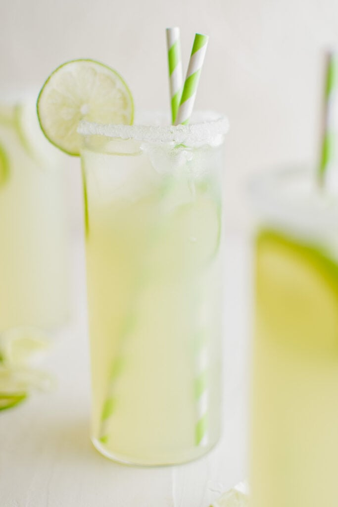 glass of limeade with a slice of lime and green straws