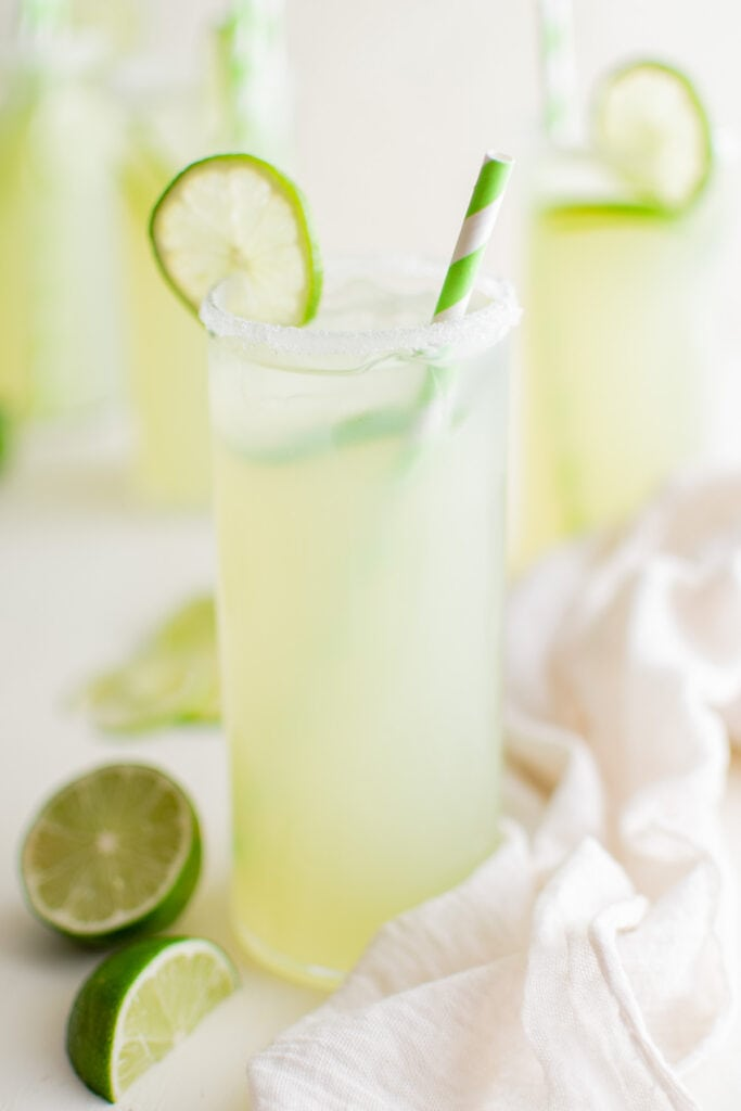 glass of limeade with limes