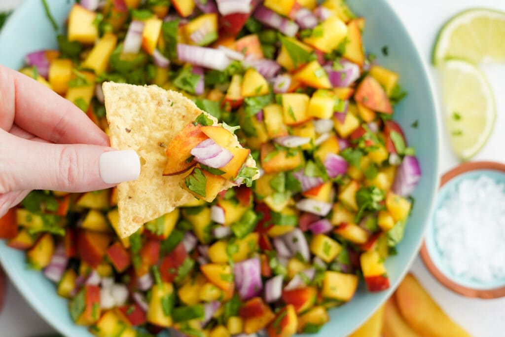 hand holding a chip dipped in peach salsa