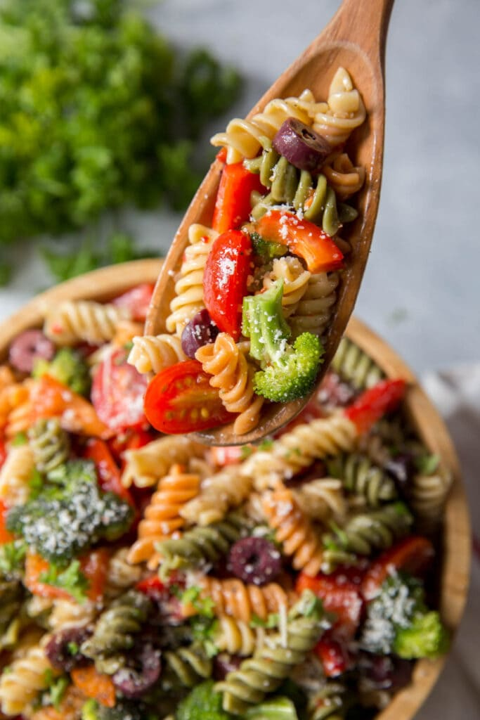 pasta, vegetables in a wood bowl with a wood spoon
