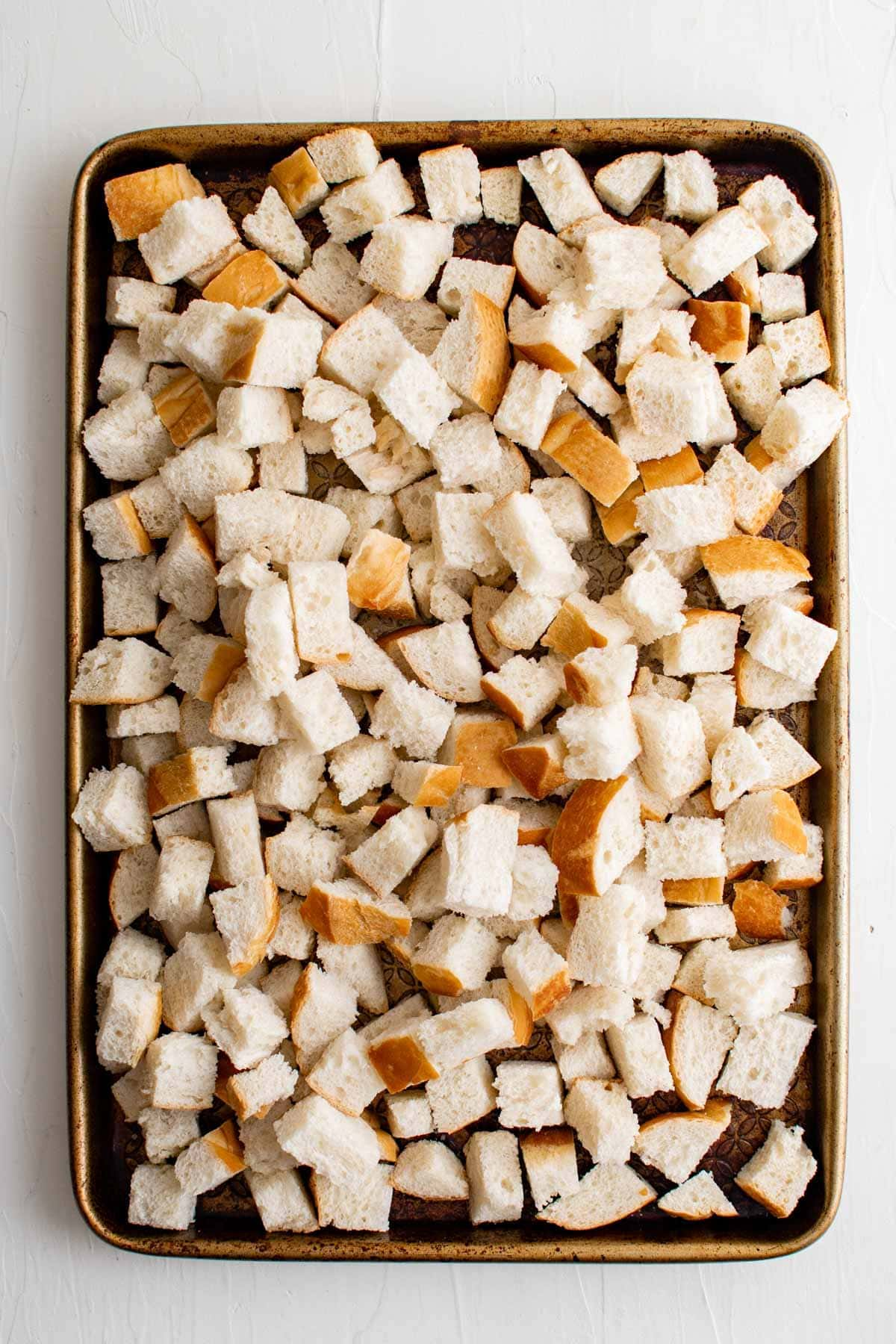 cubes of french bread on a baking sheet.