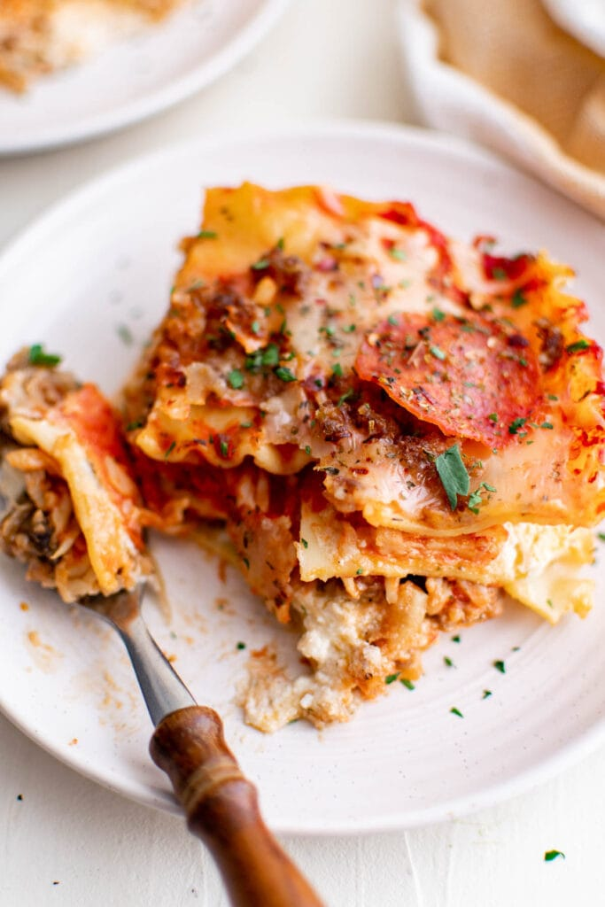 lasagna on a white plate and a fork
