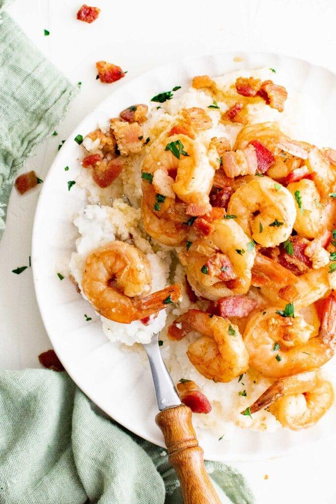 shrimp, grits, white plate, fork, green napkin