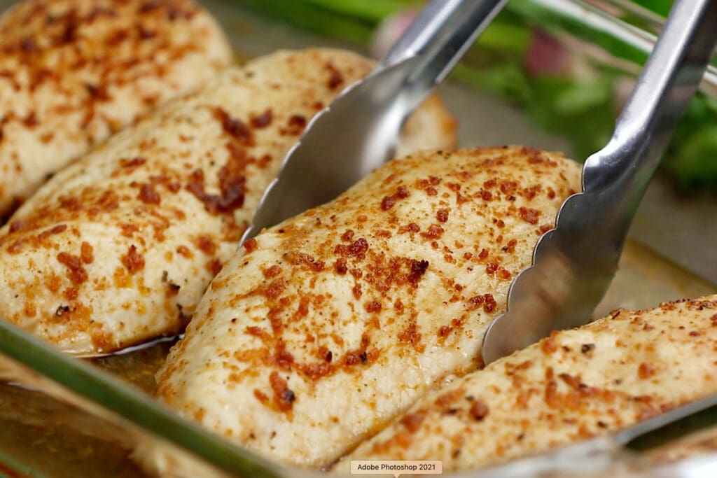 baked chicken breasts and tongs