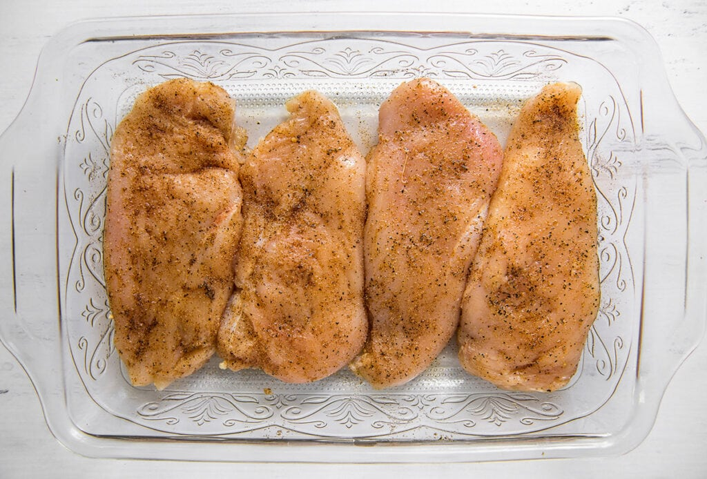 chicken breasts in a glass dish with seasoning