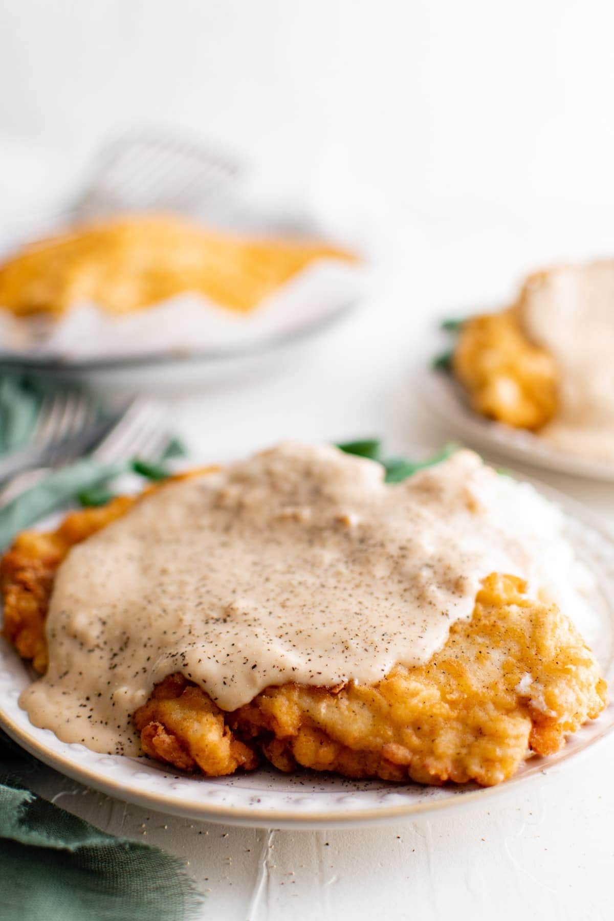 chicken fried chicken with gravy on a plate with green beans and mashed potatoes