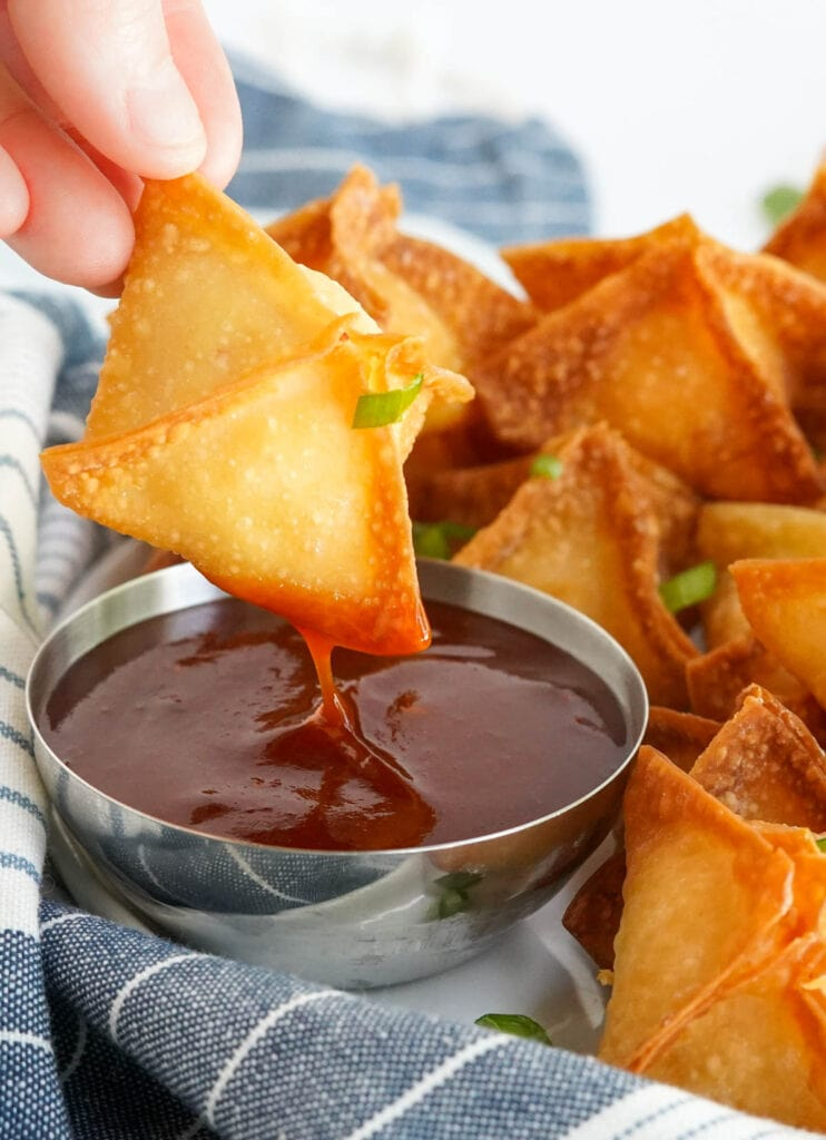 crab rangoon dipped into a red chile sauce