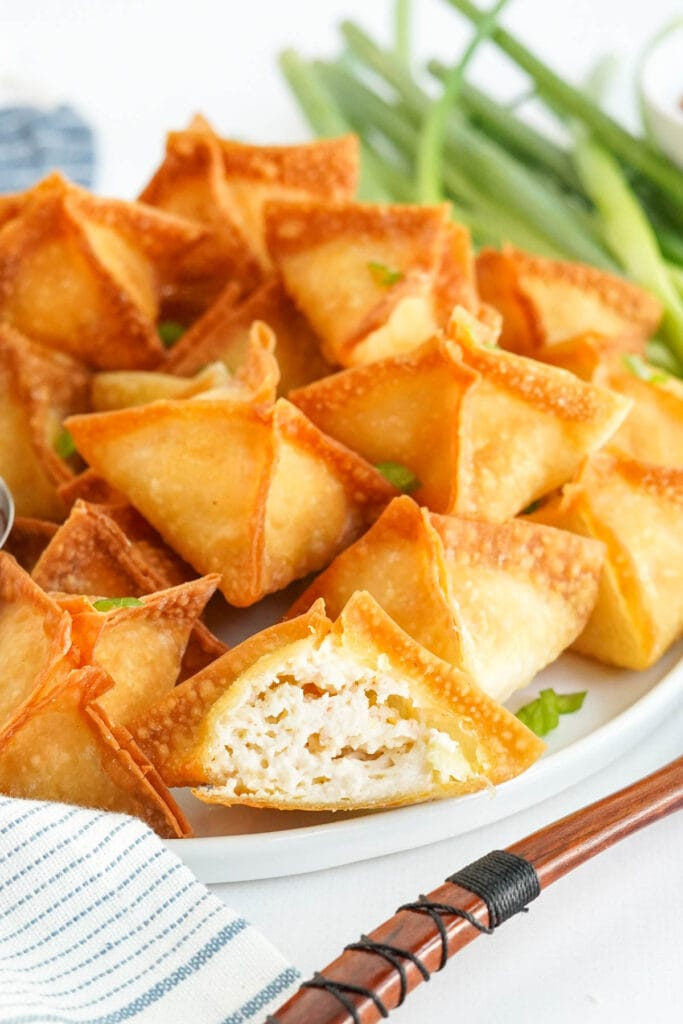 plate of wontons, one is cut in half to show the filling