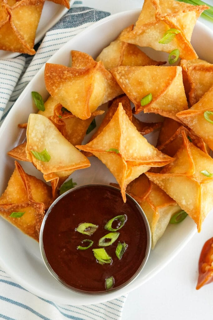 crab rangoon fried wontons on a white plate with a dipping sauce
