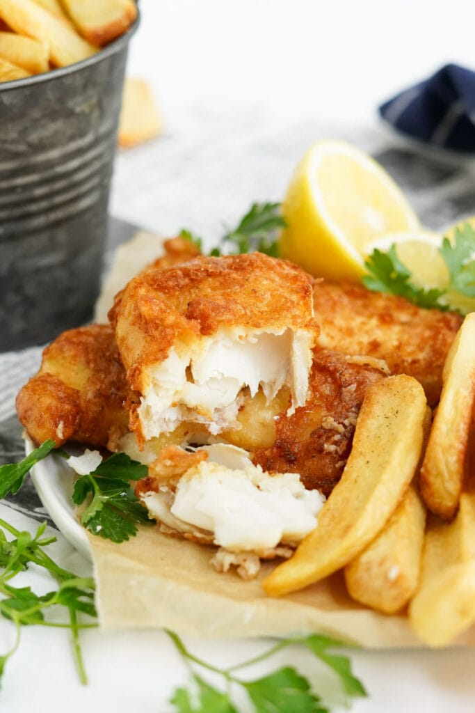 fish and chips in a basket, showing the inside of the flaky white fish
