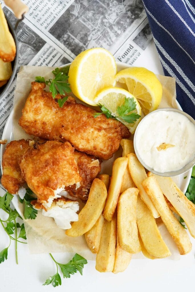 fried fish and chips in a basket with tartar sauce and lemons