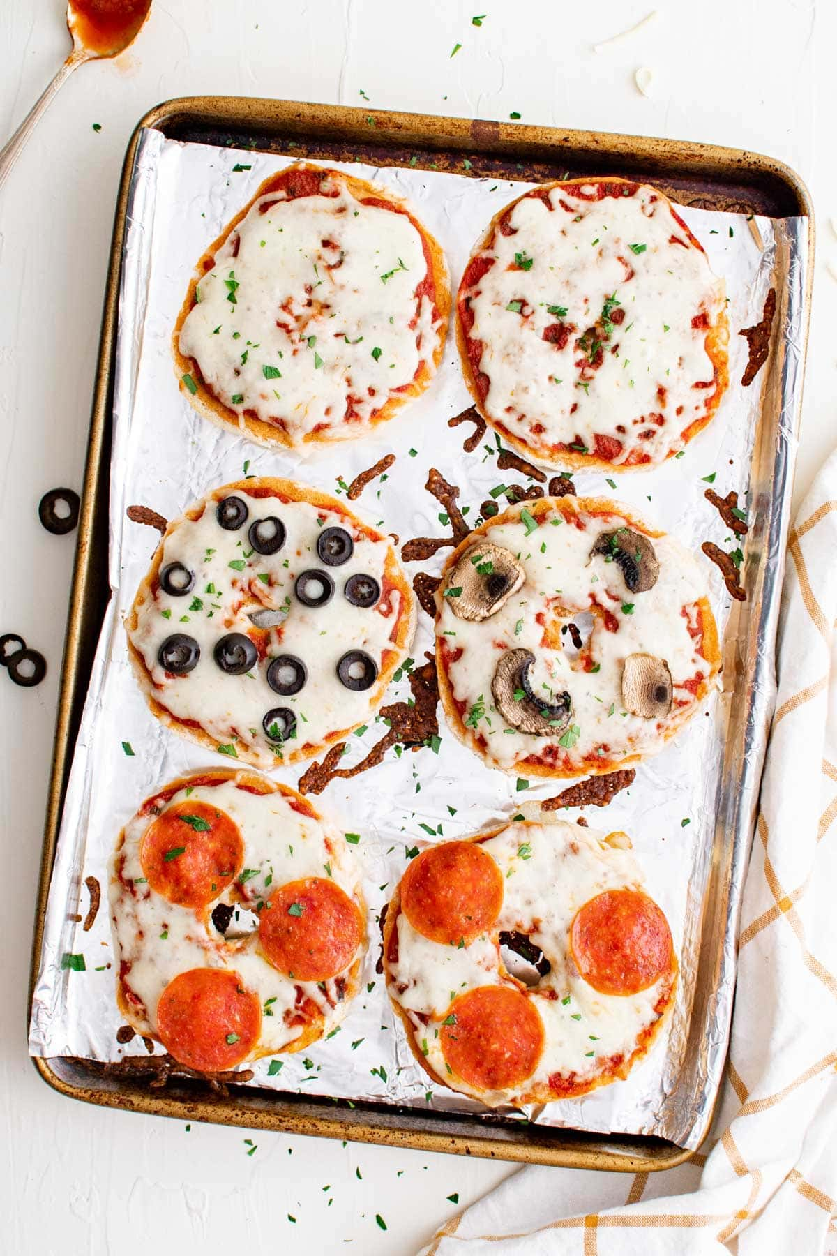 pizza bagels on a baking sheet