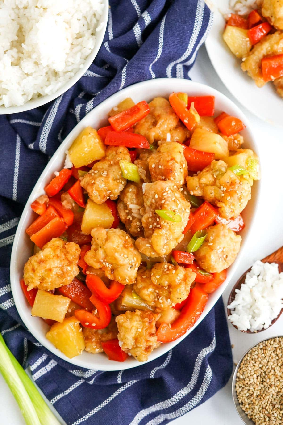 sweet and sour chicken with bell peppers and pineapple on a white platter