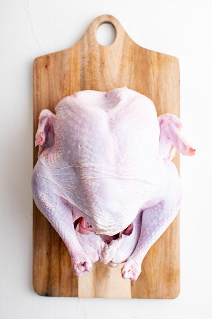 raw whole turkey on a cutting board