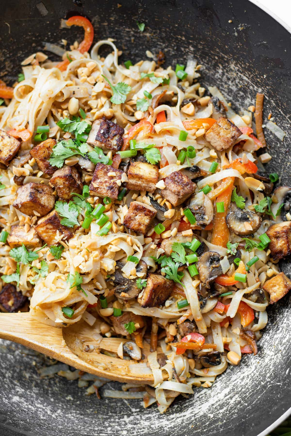 pad thai noodles with vegetables and tofu in a skillet