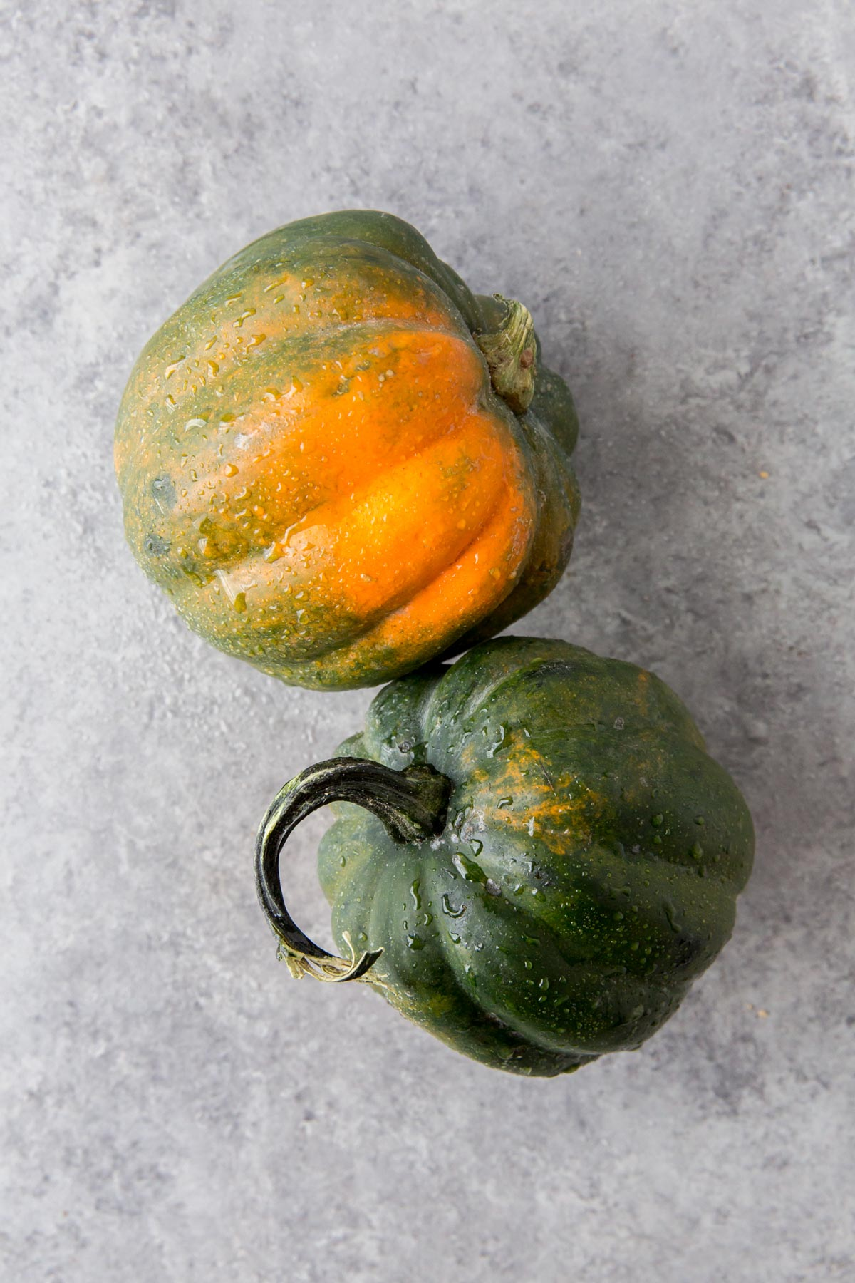 2 whole acorn squash on a gray background