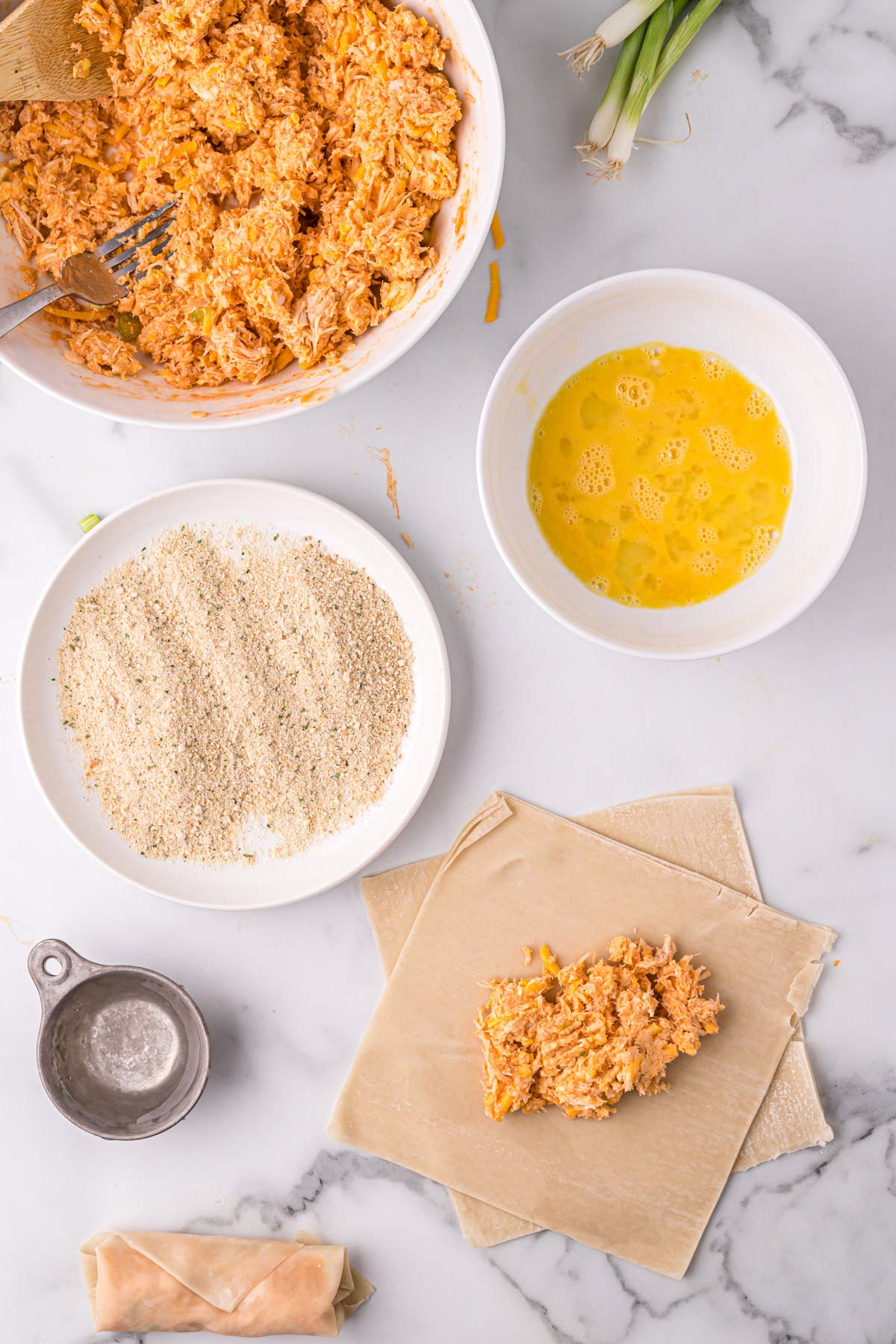 buffalo chicken, dishes of breadcrumbs, egg and egg roll wrappes