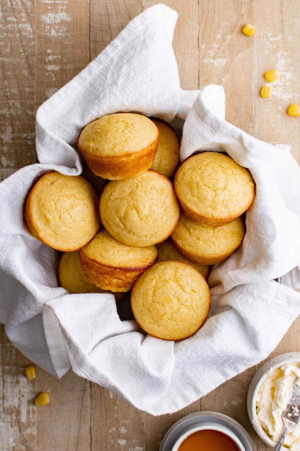 basket with a white towel filled with cornbread muffins