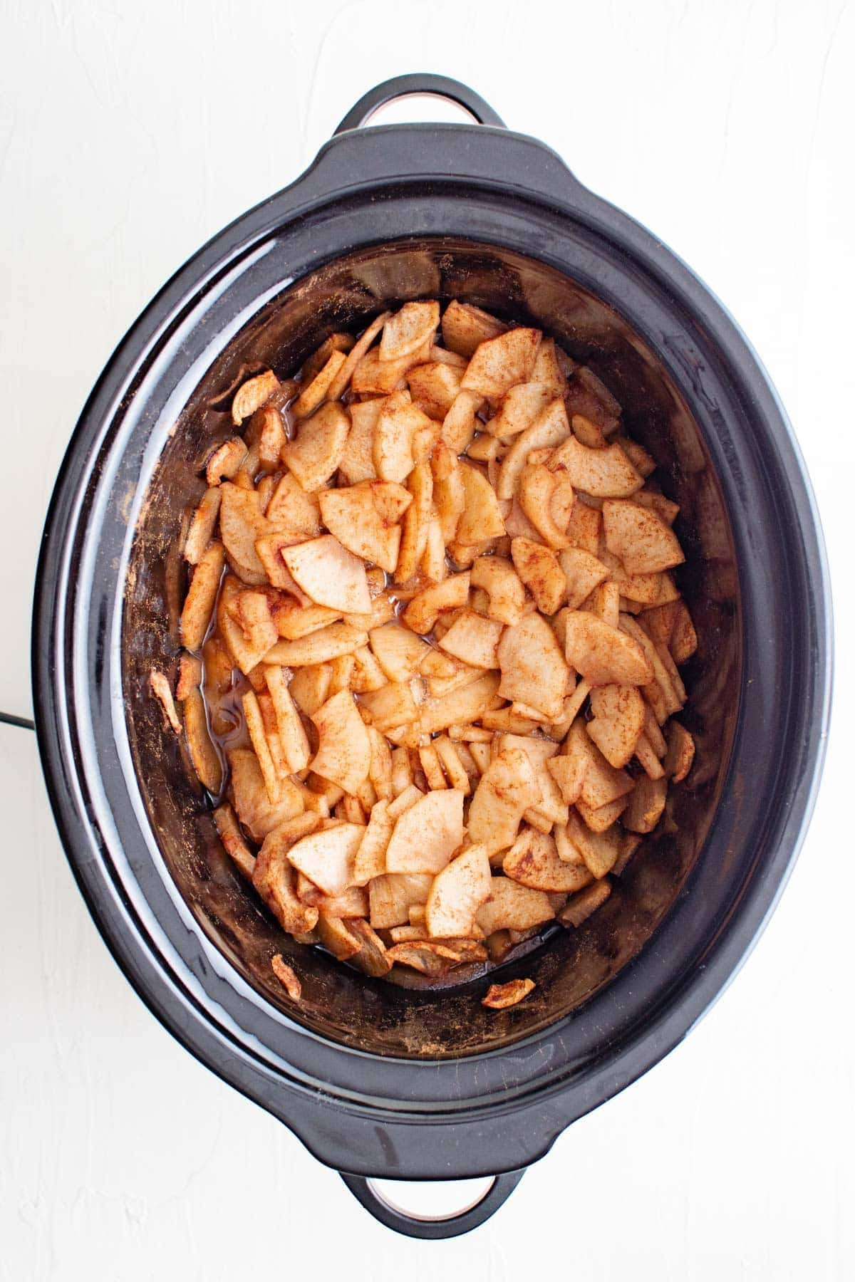 apples coated with cinnamon and sugar in a slow cooker