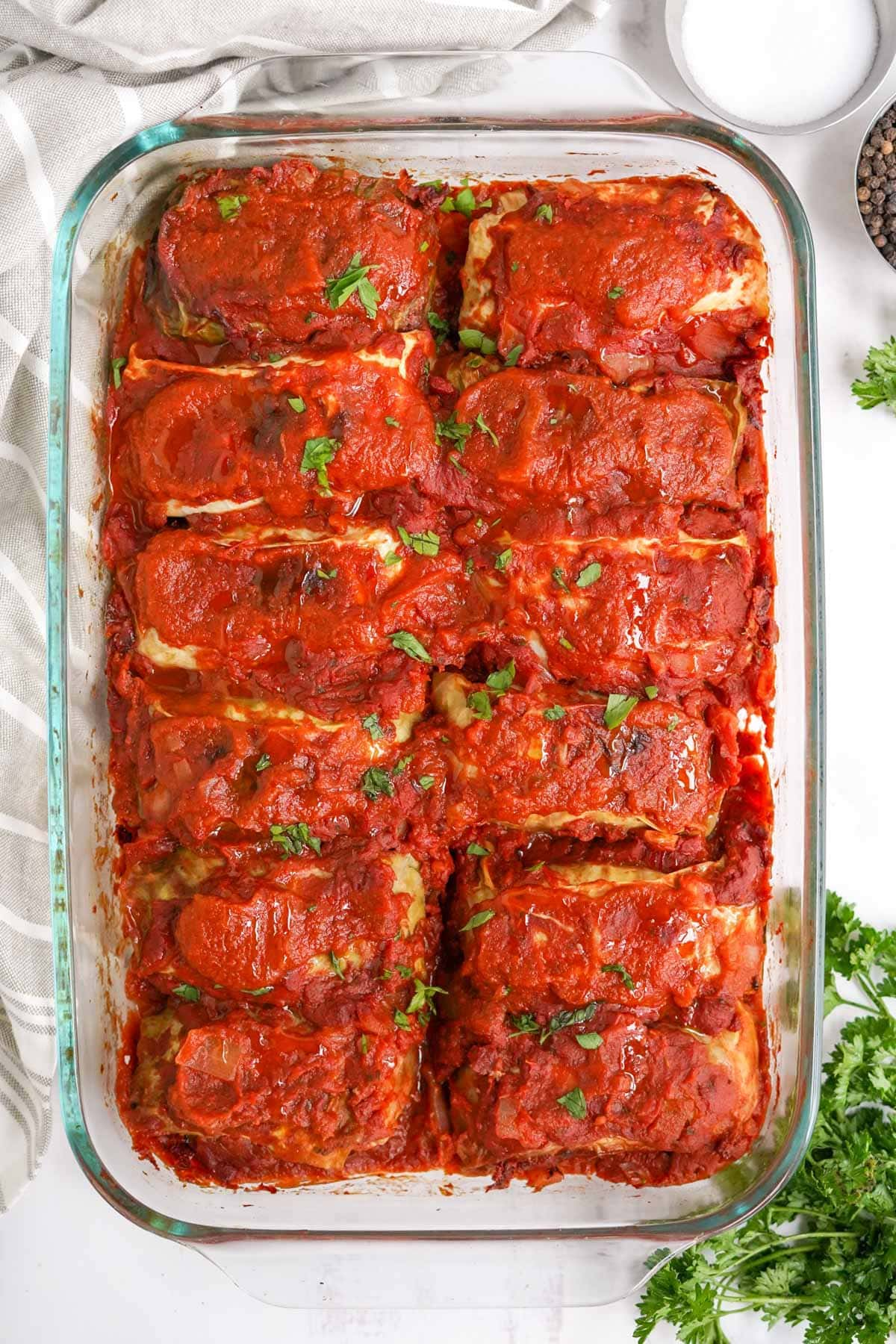 clear glass baking dish with cabbage rolls and sauce