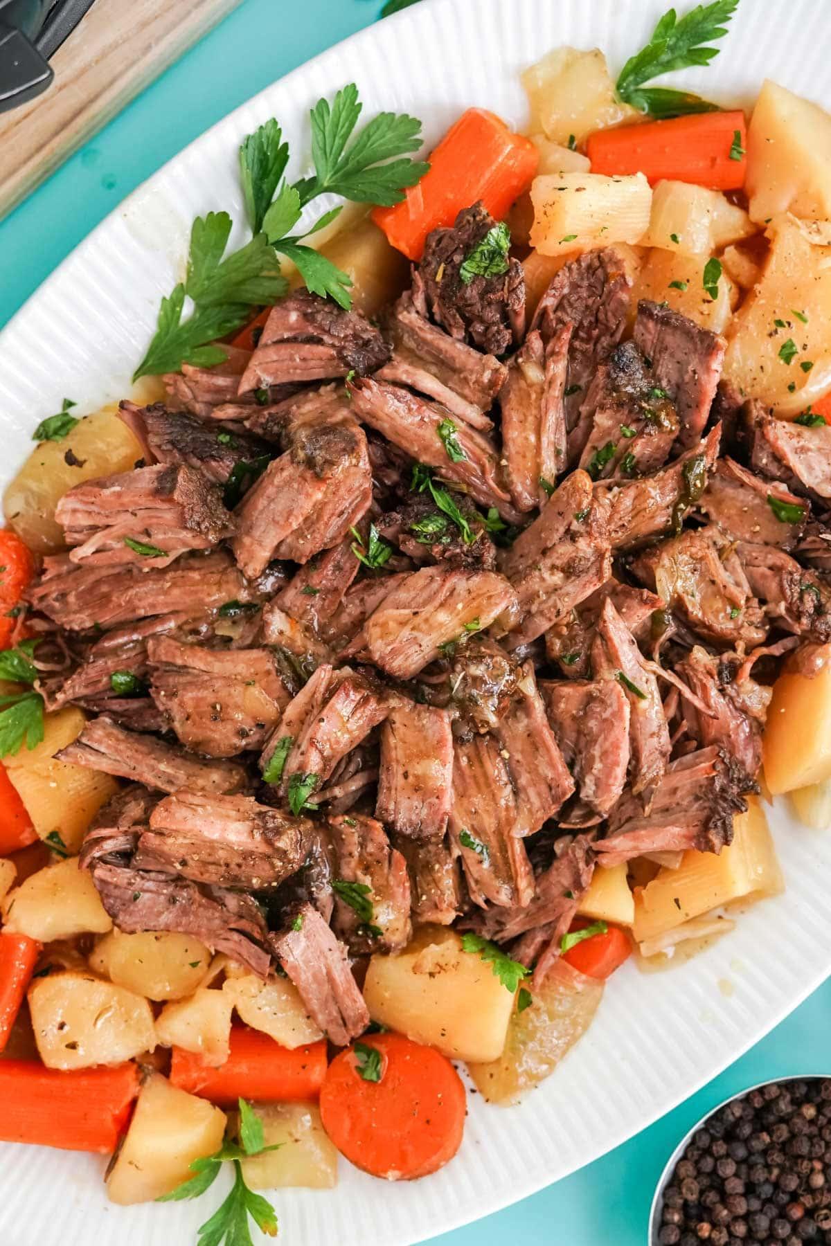 shredded pot roast, carrots and potatoes on a platter