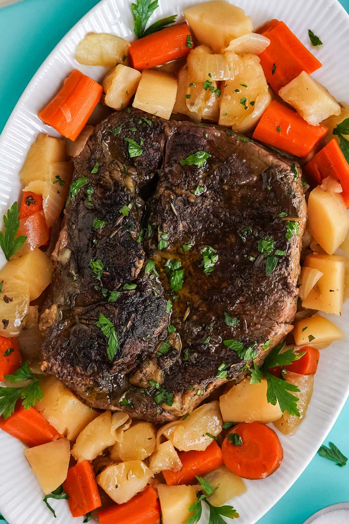 chuck roast, carrots, onions, potatoes on white serving platter