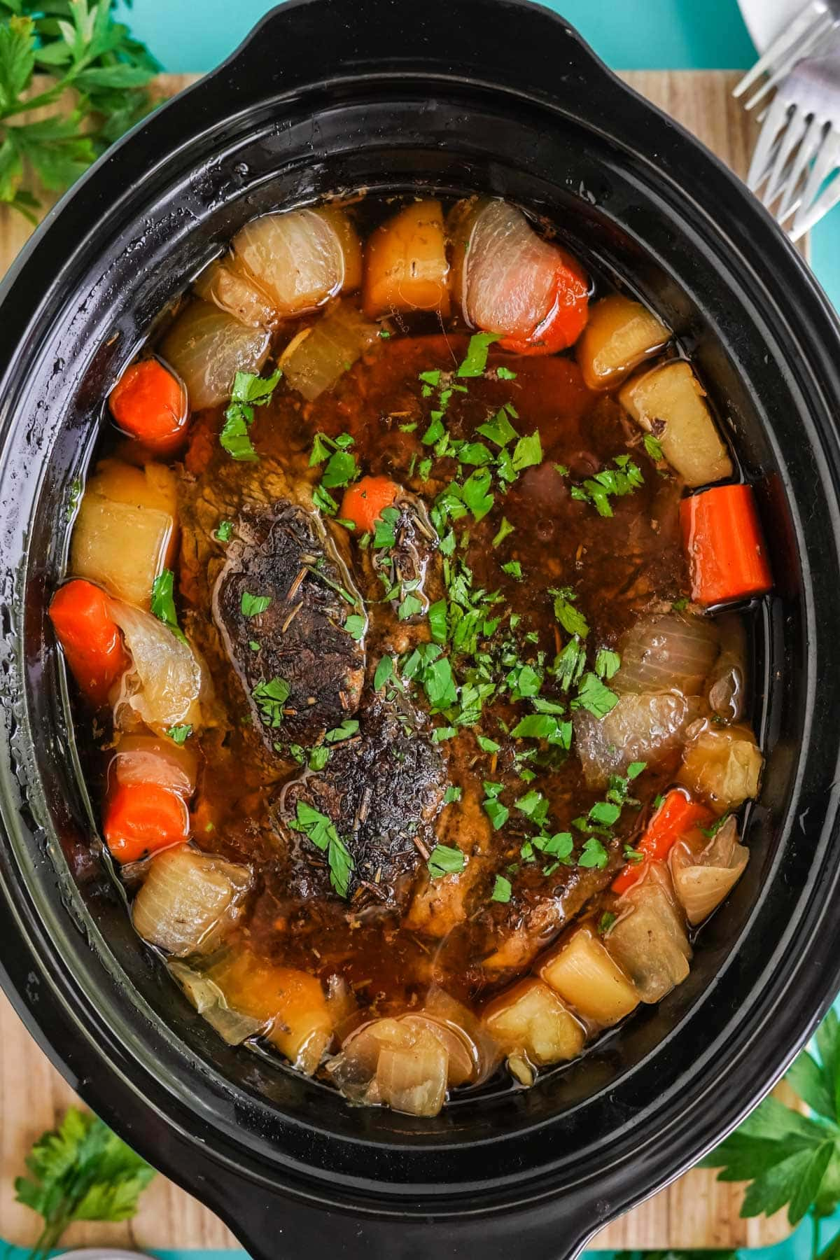 chuck roast in a slow cooker surrounded by potatoes and carrots with parsley on top