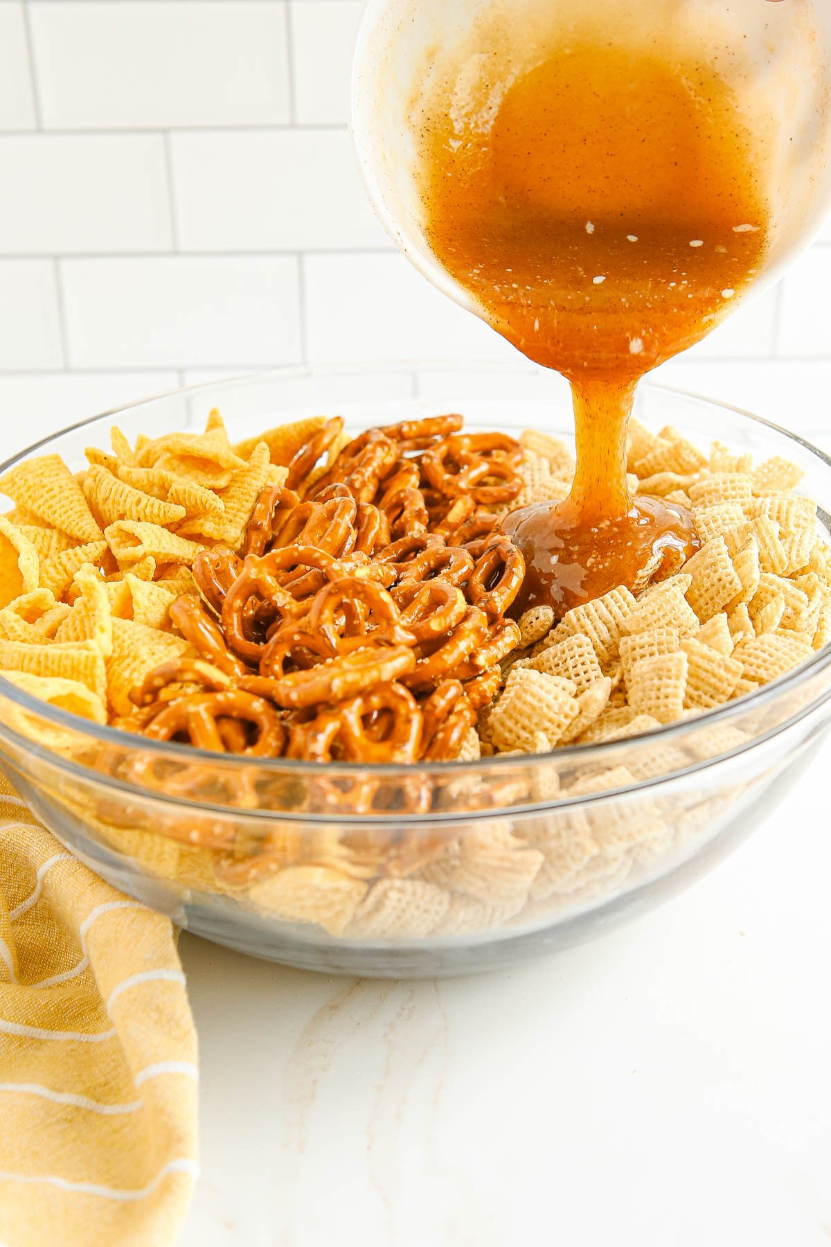 large glass bowl with bugles, pretzels and chex cereal, butter and brown sugar sauce pouring over